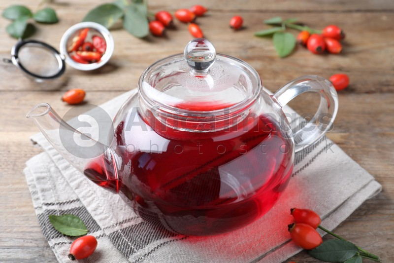 Teapot with aromatic rose hip tea and fresh berries on wooden table