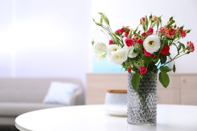 Vase with beautiful flowers on white table in room, space for text