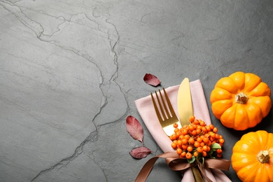 Cutlery, rowan berries and pumpkins on grey table, flat lay with space for text. Thanksgiving Day