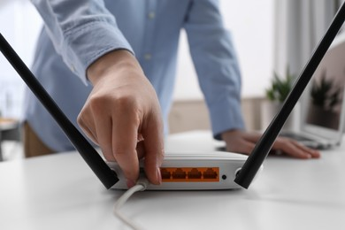 Woman connecting cable to router at white table indoors, closeup. Wireless internet communication