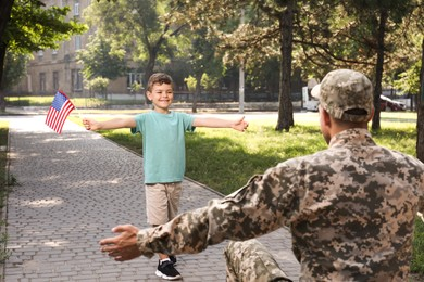 Little boy with flag of USA running towards his father in military uniform outdoors. Family reunion