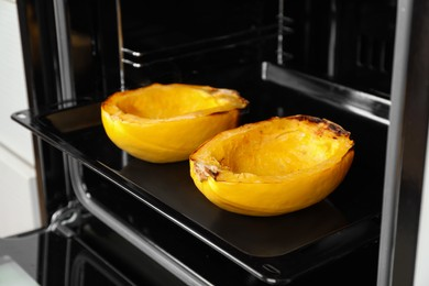 Baking sheet with halves of cooked spaghetti squash in oven