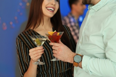 Young couple with martini cocktails at party, closeup