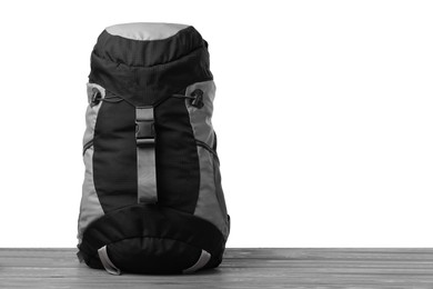 Hiking backpack on wooden surface against white background. Space for text