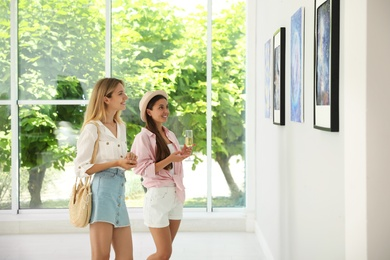 Young women at exhibition in art gallery