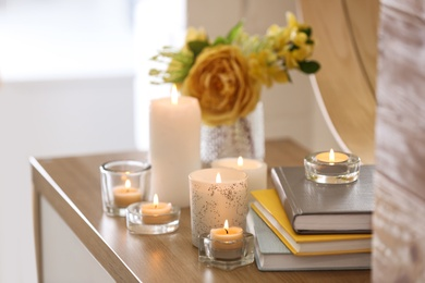 Beautiful burning candles, books and flowers on table at home