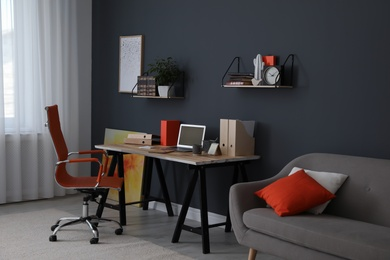 Modern workplace with comfortable chair in stylish home office interior