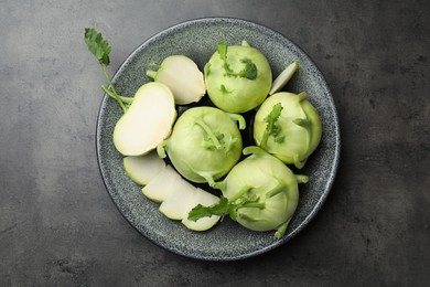Whole and cut kohlrabi plants on grey table, top view
