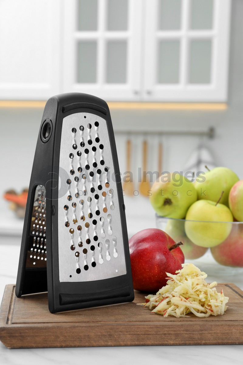 Grater and fresh ripe apples on white table in kitchen