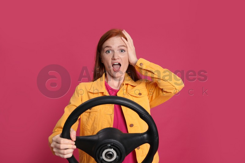 Emotional young woman with steering wheel on crimson background