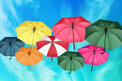 Group of different colorful umbrellas against blue sky with white clouds on sunny day