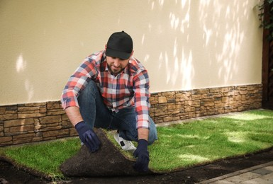 Young man laying grass sod on ground at backyard, space for text