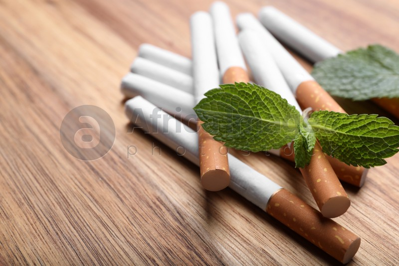 Menthol cigarettes and mint leaves on wooden table, closeup. Space for text