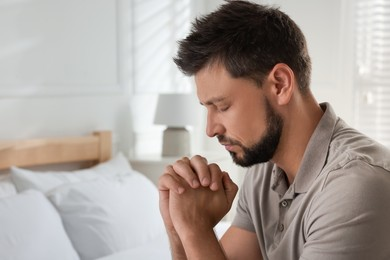 Religious man praying in bedroom. Space for text
