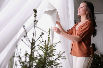 Woman putting decorative star on window at home
