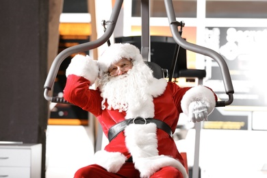 Authentic Santa Claus resting after exercise in modern gym