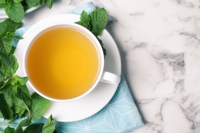Fresh tea with mint on white marble table, flat lay