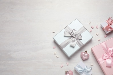 Beautiful gift boxes and festive decor on white table, flat lay. Space for text
