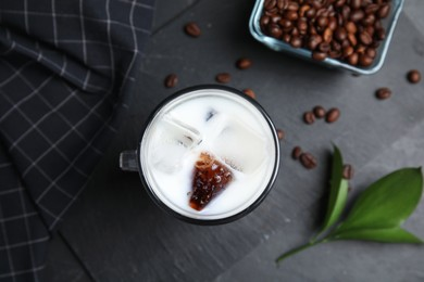 Glass cup of milk with delicious grass jelly, green leaf and coffee beans on black table, flat lay