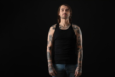Young man with tattoos on body against black background
