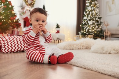 Cute baby wearing bright pajamas on floor in room decorated for Christmas