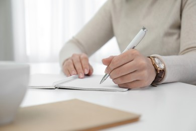 Left-handed woman writing in notebook at table indoors, closeup. Space for text