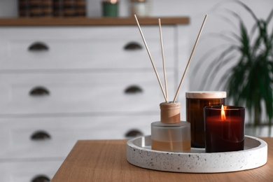 Air reed freshener and candles on table in living room. Space for text