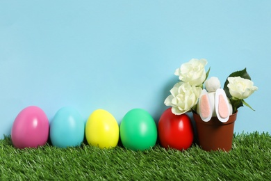 Bright Easter eggs, pot with flowers and toy bunny on green grass against light blue background