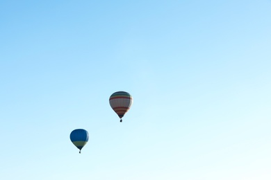 Colorful hot air balloons flying in blue sky. Space for text