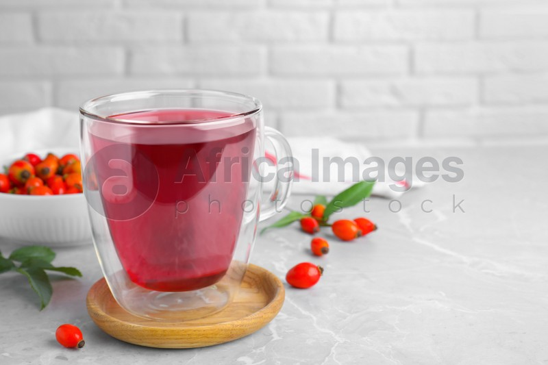 Aromatic rose hip tea and fresh berries on light grey marble table, space for text