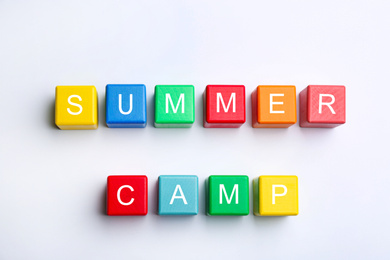 Colorful wooden cubes with phrase SUMMER CAMP on white background, top view