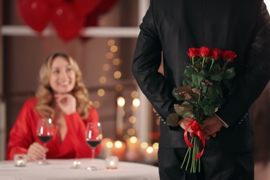 Man hiding roses for his beloved woman in restaurant at Valentine's day dinner