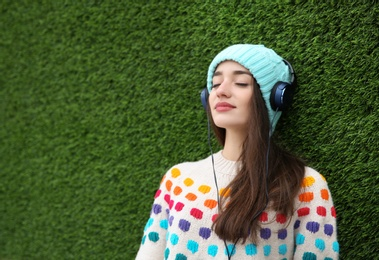 Beautiful young woman listening to music with headphones near grass wall. Space for text