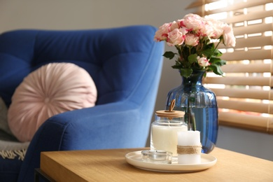 Vase with beautiful flowers and candles on wooden table indoors, copy space text. Interior elements