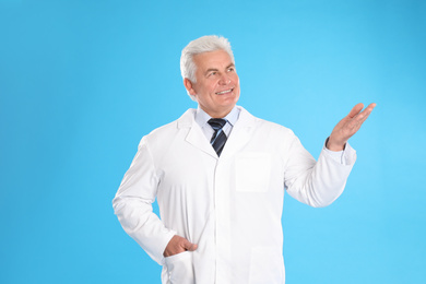Happy senior man in lab coat on light blue background