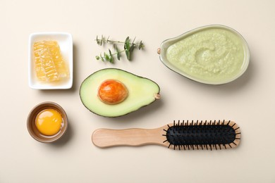 Homemade hair mask in bowl, fresh ingredients and wooden brush on beige background, flat lay