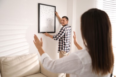 Happy couple decorating room with picture together. Interior design