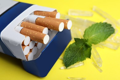 Pack of cigarettes, menthol crystals and mint on yellow background, closeup