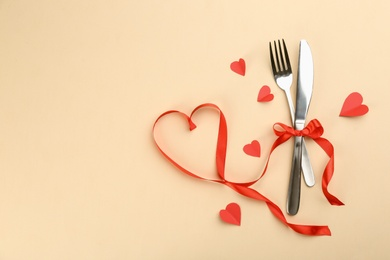 Beautiful cutlery set, hearts and red ribbon on beige background, flat lay with space for text. Valentine's Day dinner