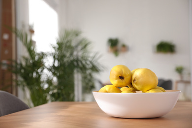 Ripe quinces on wooden table at home
