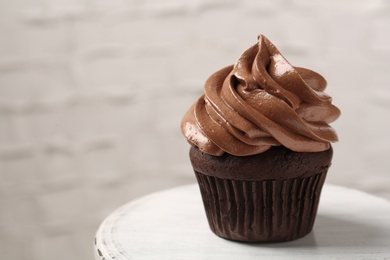 Delicious chocolate cupcake with cream on white table, closeup. Space for text