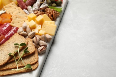 Different tasty appetizers on light marble table, closeup. Space for text