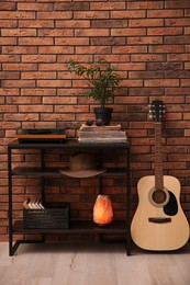 Stylish turntable, guitar and vinyl records on shelving unit near red brick wall indoors