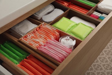 Storage of different feminine hygiene products in wooden drawer, closeup