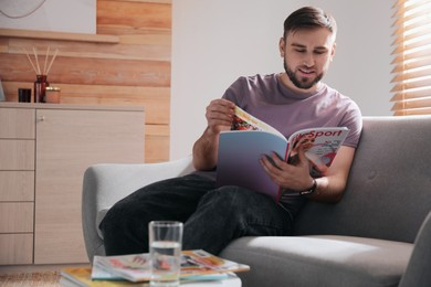 Young man reading sports magazine on sofa at home