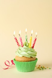 Birthday cupcake with burning candles, streamer and sprinkles on beige background