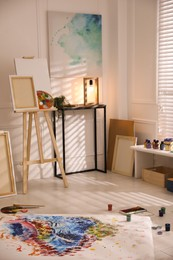Wooden easel and abstract picture in art studio