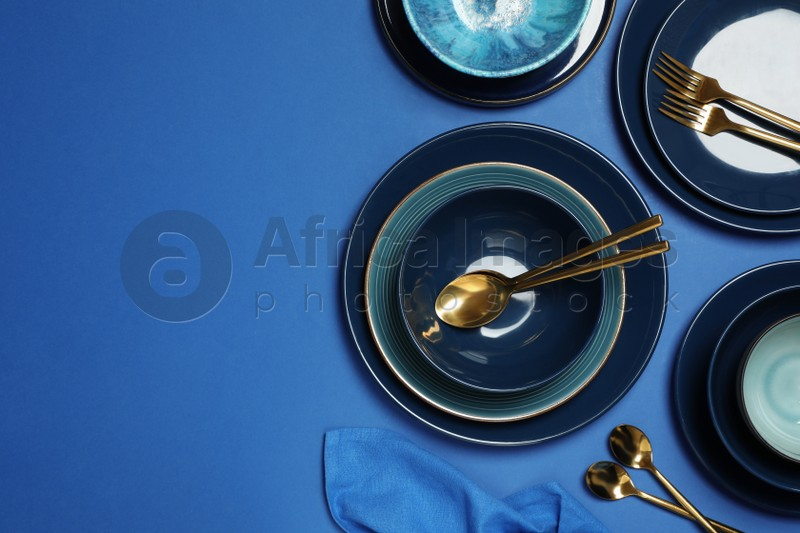 Clean dishware and cutlery on blue background, flat lay. Space for text