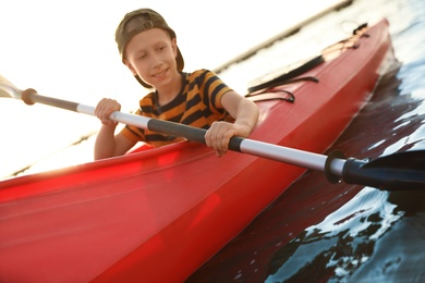 Happy little boy kayaking along river, focus on paddle. Summer camp activity