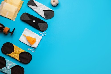 Cloth menstrual pads and other female hygiene products on light blue background, flat lay. Space for text